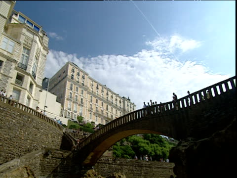 Pan left from footbridge to cream painted Victorian buildings Biarritz South of France