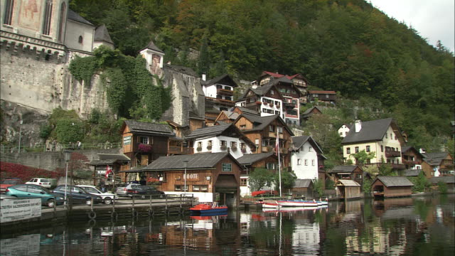 Pan left from lakeside buildings reflected in Hallstattersee to Catholic church above, Hallstatt