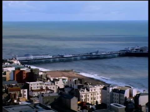 pan left from new pier to beach and coastal seaside town - brighton england stock videos and b-roll footage