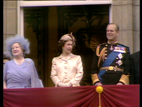Pan left from Queen Elizabeth II and Prince Phillip to Queen Mother waving as crowds sing happy birthday to her London 15 Jul 80