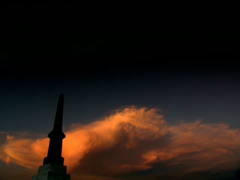 pan left from silhouetted memorial to the 24th regiment at isandhlwana against orange cloud in dark sky with half moon - half moon stock videos & royalty-free footage