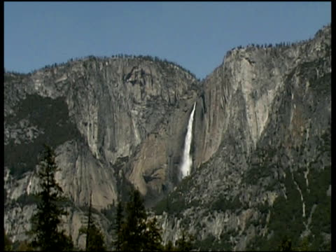 pan left from waterfall in center of cliff face across mountains with pine trees in foreground yosemite national park - yosemite stock videos and b-roll footage