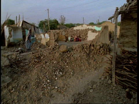 ms pan left gujarat, indian families amongst rubble of collapsed homes, after earthquake, gujarat, india - グジャラート州点の映像素材/bロール