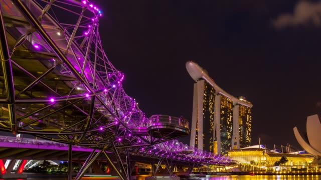tl pan left, helix bridge across marina bay and singapore skyline at night - helix bridge stock videos & royalty-free footage