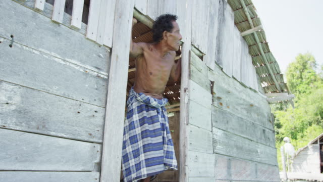 pan left, man looks out entrance to fishing hut in indonesia - poverty stock videos & royalty-free footage