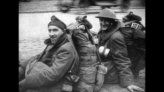 vidéos et rushes de pan left of american soldiers resting at the street of a french village / jovial solder speaks as a comrade grins / train laden with wheeled... - soldat