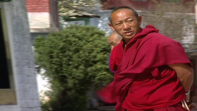 pan left on tibetan buddhist monks conversing and strolling near the entrance to the library of tibetan works and archives, which holds over 80000... - traditionally tibetan stock videos & royalty-free footage