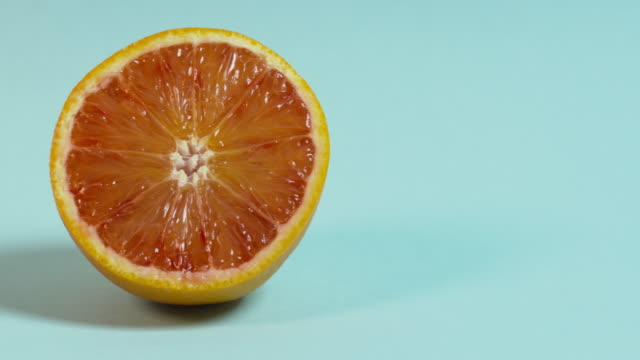 Pan left onto, then off, a cross-section of an orange against a plain blue background.