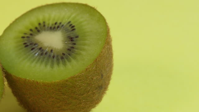 pan left onto, then off, a kiwi fruit cut in half against a plain background. - ascorbic acid stock videos & royalty-free footage
