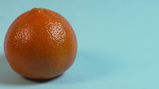 pan left onto, then off, a whole orange on a plain, pale blue studio background. - ascorbic acid stock videos & royalty-free footage