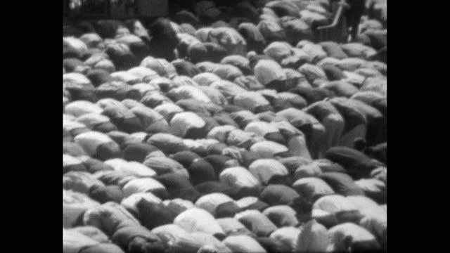 pan left over a large crowd of muslim men kneeling in prayer together in amman, jordan; 1967. - harmony stock videos & royalty-free footage