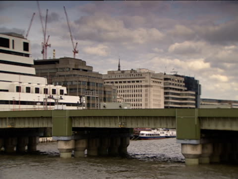 pan left over cannon street rail bridge to skyline featuring nat west tower and partially-built 30 st mary axe (also known as 'gherkin') london - bridge built structure stock videos & royalty-free footage