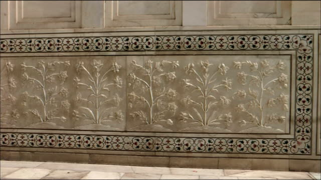 vídeos de stock, filmes e b-roll de pan left over carvings of flowers and grasses at taj mahal, agra - mausoleum