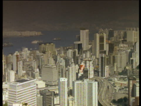 pan left over city skyline with harbor in distance trees in foreground - central district hong kong stock videos and b-roll footage