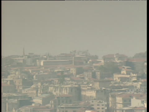 pan left over city skyline with mosques in a misty light istanbul - turchia video stock e b–roll