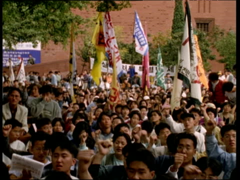 Pan left over crowd of students calmly protesting by rhythmically waving their fists Seoul 1997