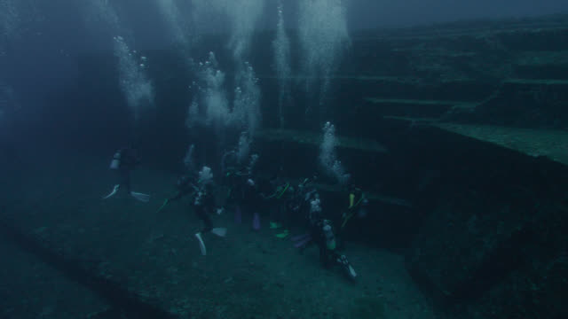 pan left over divers investigating yonaguni monument. japan - archaeology stock videos & royalty-free footage