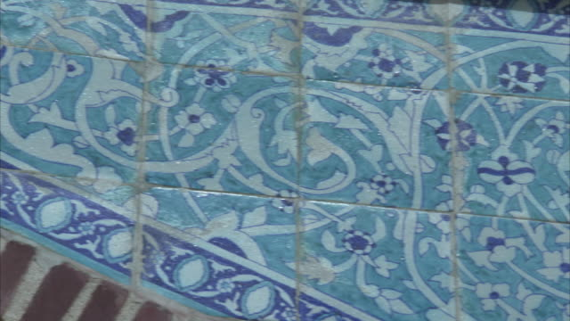 Pan left over elaborately designed blue and white tiles within interior of Shah Jahan mosque Available in HD.