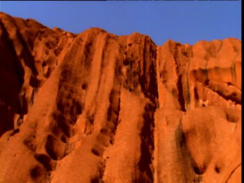 pan left over glowing red sandstone of uluru in outback, northern territory, australia - sandstone stock videos & royalty-free footage