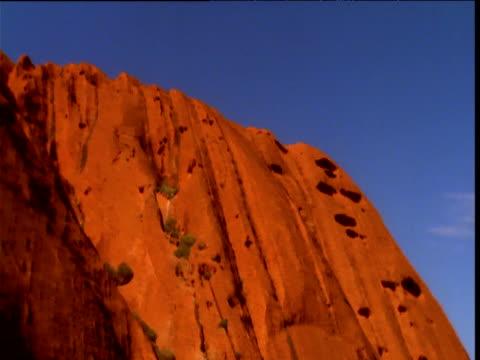 pan left over glowing red sandstone of uluru in outback, northern territory, australia - エアーズロック点の映像素材/bロール