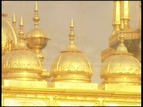 pan left over gold mini domes on golden temple roof tilt down to gold covered suspended bay window - bay window stock videos & royalty-free footage