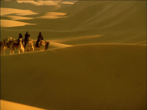 Pan left over golden desert dunes to robed travellers riding and leading camel caravan up ridge