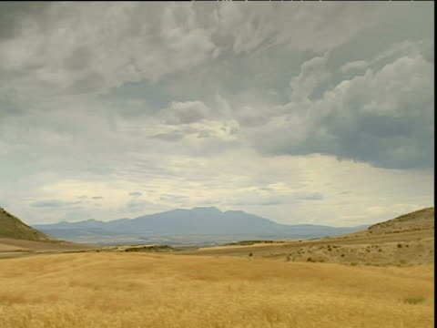 pan left over golden plain with mountains in distance central spain - plateau stock videos and b-roll footage