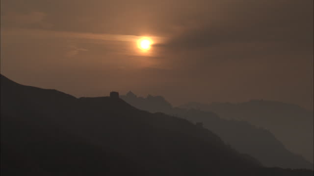 Pan left over Great wall of China at Badaling silhouetted by setting sun, Beijing.