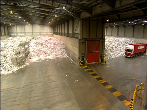 pan left over large paper recycling depot to bulldozer moving paper - stil der 2000er jahre stock-videos und b-roll-filmmaterial