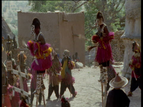 Pan left over line of dancers and stilt walkers performing traditional remembrance/funeral dance, Mali