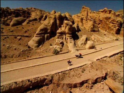 pan left over man on horse galloping along road with rocky hills in background petra jordan - galoppera bildbanksvideor och videomaterial från bakom kulisserna