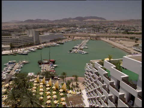 pan left over marina and hotels eilat - 室外プール点の映像素材/bロール