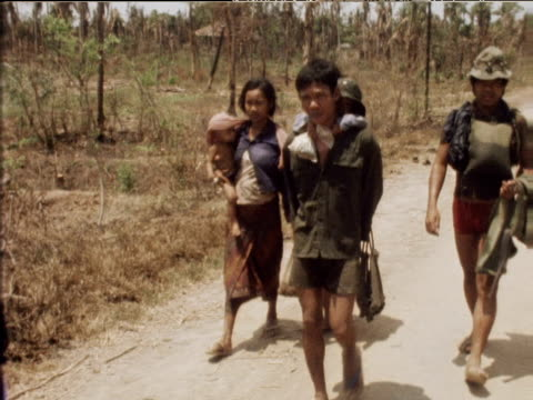 vídeos de stock, filmes e b-roll de pan left over military reinforcements walking down road with wives and children to frontline cambodia mar 75 - cambodia