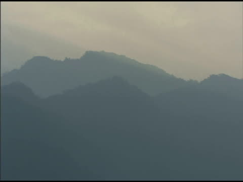 pan left over misty forested mountains - rolling landscape stock videos & royalty-free footage