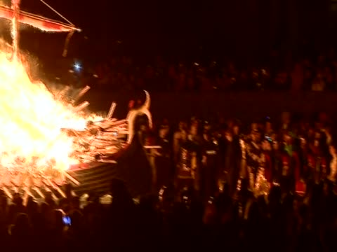 pan left over people watching the burning replica viking galley at the culmination of the up helly aa festival - flaming torch stock videos & royalty-free footage