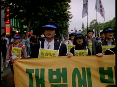 Pan left over protesters carrying large green and yellow banner marching down street Seoul 1997