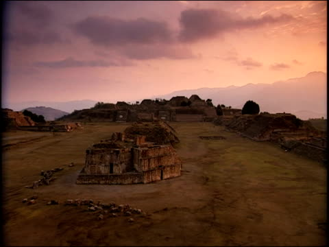 vidéos et rushes de pan left over remains of maya city under purple dusk sky, mexico - maya