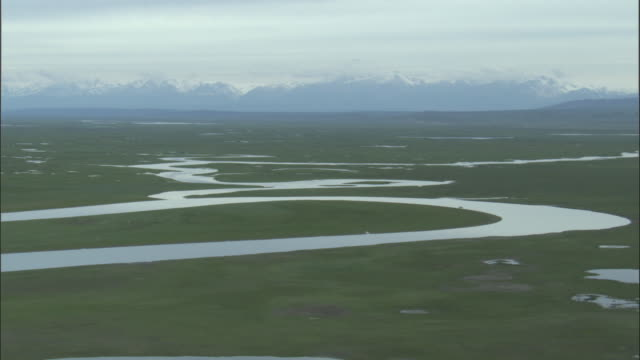 Pan left over river meandering through grassland, Bayanbulak grasslands.