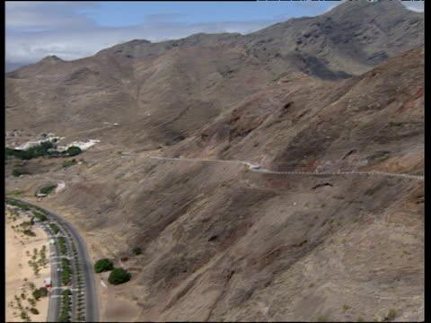 pan left over rocky mountains tilt down to main road and teresita artificial sandy beach - 大西洋諸島点の映像素材/bロール