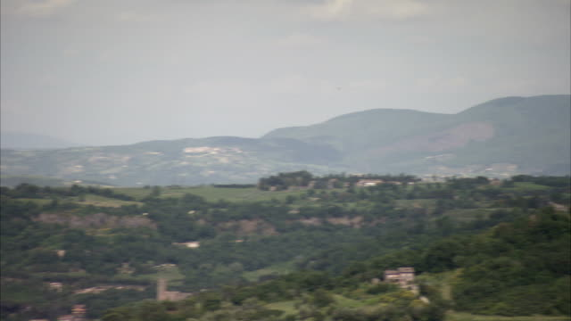 pan left over rolling countryside to the orvieto cathedral towering over the town. available in hd. - kirchturmspitze stock-videos und b-roll-filmmaterial