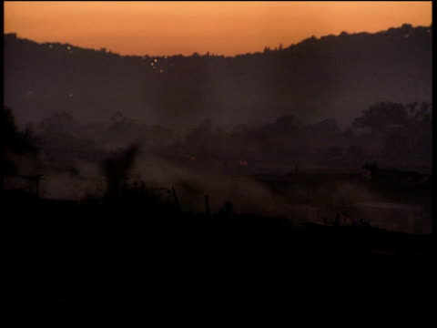 pan left over roof tops at sunrise with mountains in background - soweto stock videos and b-roll footage
