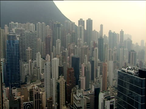 pan left over skyscrapers at foot of victoria peak hong kong - ビクトリアピーク点の映像素材/bロール