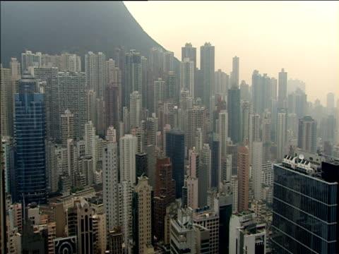 pan left over skyscrapers at foot of victoria peak hong kong - berg victoria peak stock-videos und b-roll-filmmaterial