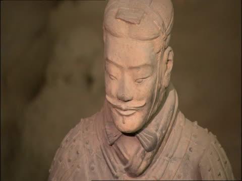 pan left over terracotta warrior faces, museum of qin, xian, china - terrakotta armee stock-videos und b-roll-filmmaterial