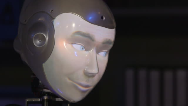 pan left over the head of a 'smiling' humanoid robothespian robot actor during rehearsals for a play, uk. - human face stock videos & royalty-free footage