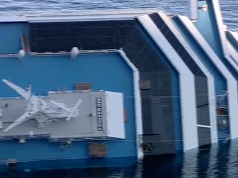 vídeos de stock e filmes b-roll de pan left over the partially submerged deck of the costa concordia. - embarcação comercial