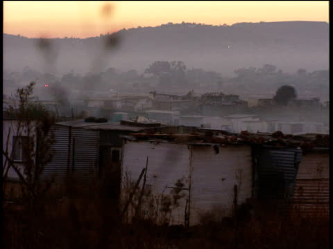 pan left over township with hills in background - soweto stock videos and b-roll footage