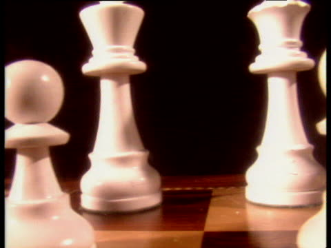 pan left over white chess pieces on board then pan right over black chess pieces - chess stock videos & royalty-free footage