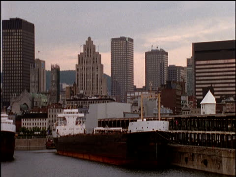 vidéos et rushes de pan left past downtown buildings and ships moored in port - montreal