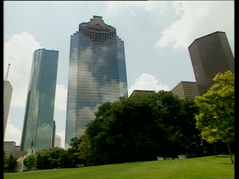 Pan left past mirrored skyscrapers with green lawn in foreground